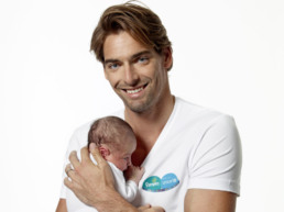 Picture of Camille Lacourt holding a baby for Pampers